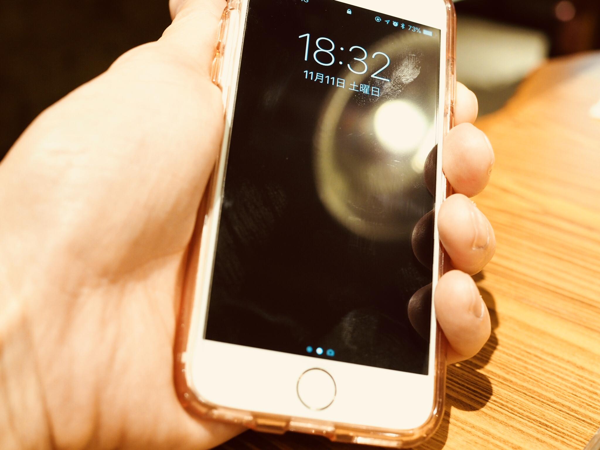 iPhoneのスリープボタンを押して、時刻を確認している